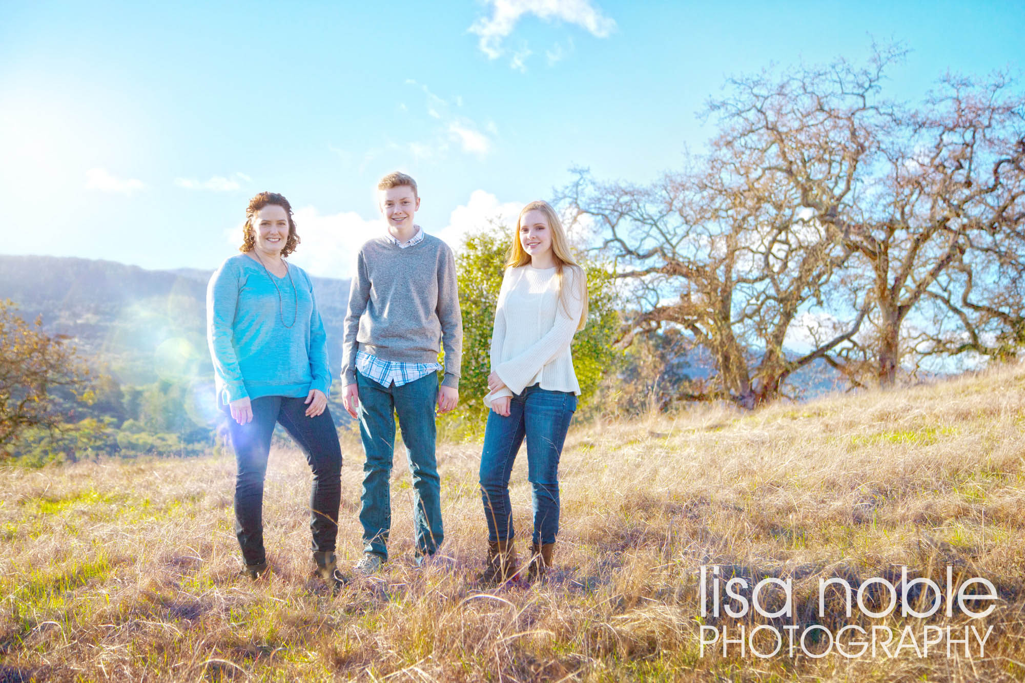 Family portrait in a grass field by Bay Area professional photographer Lisa Noble