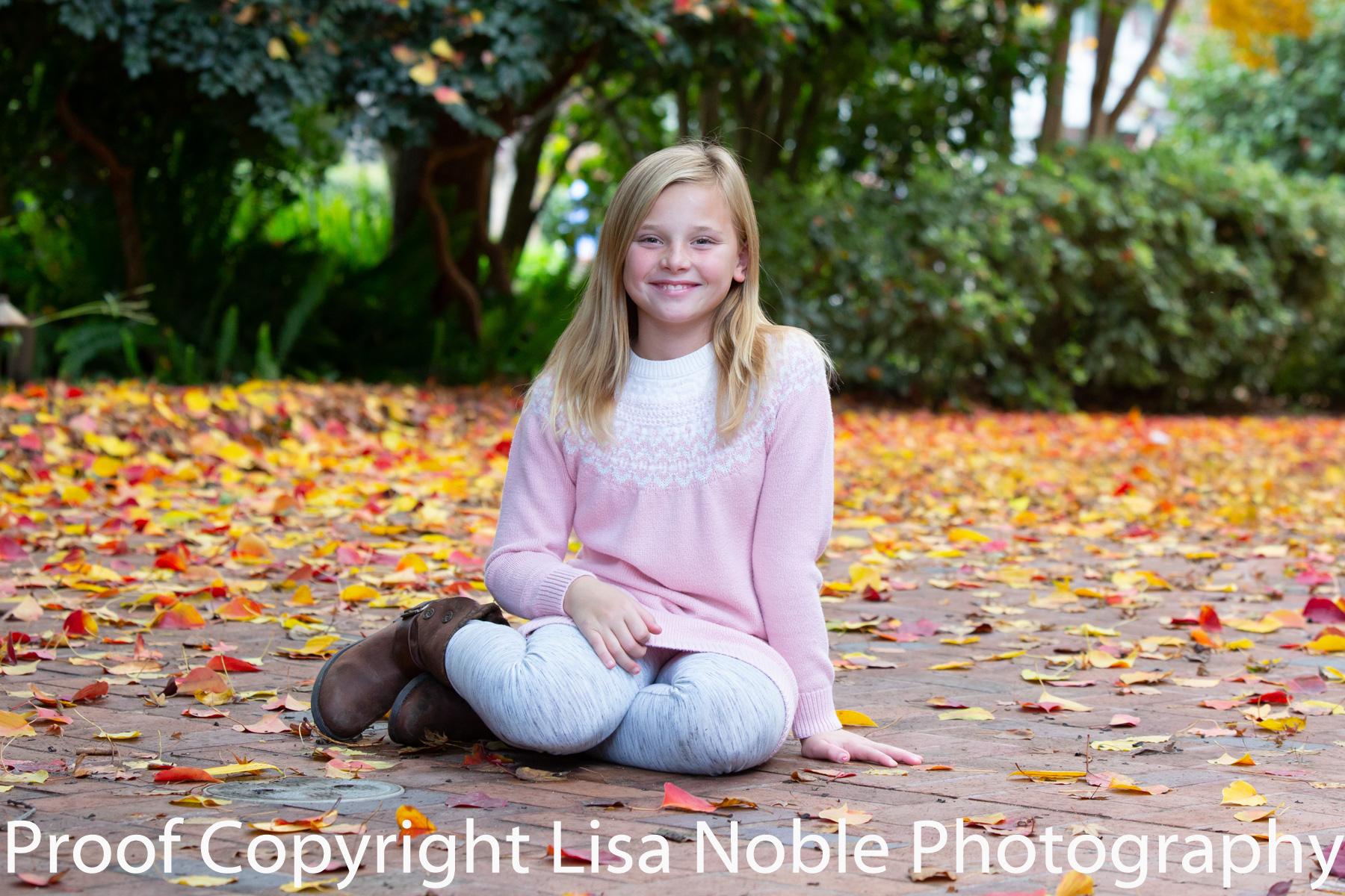 Girl sitting in leaves at photogaphy session